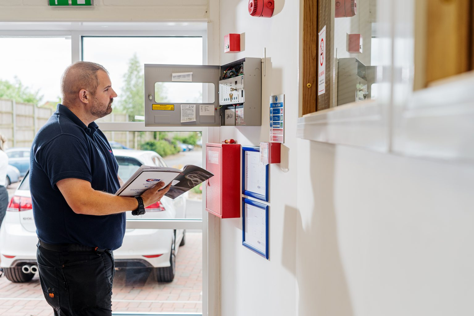 Engineer completing a risk assessment on site whilst looking at a fire alarm system