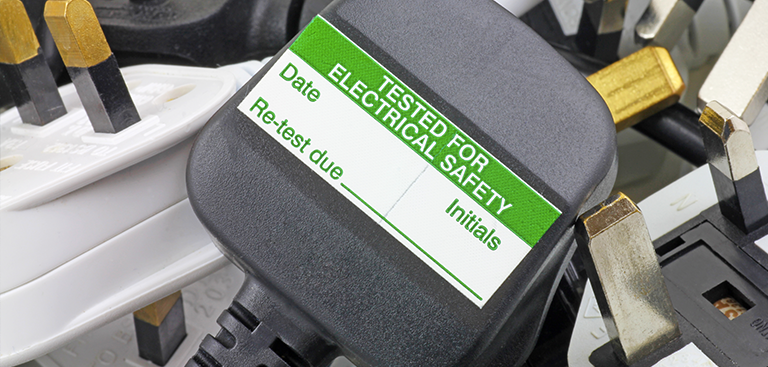 Photograph of a electronic plug with a PAT Testing sticker on