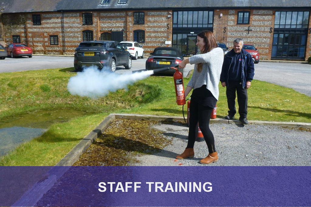 Photograph of a woman demonstrating how a fire extinguisher works following a training by Fireline UK