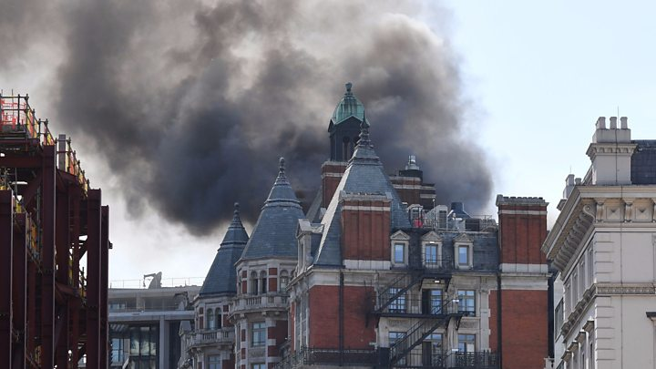 Photograph of the Mandarin Oriental Hotel on fire with thick smoke