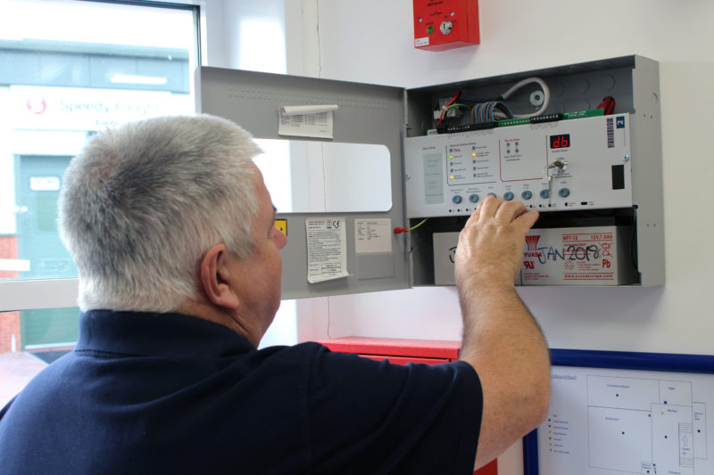 Photograph of a fireline engineer inspecting a fire alarm system